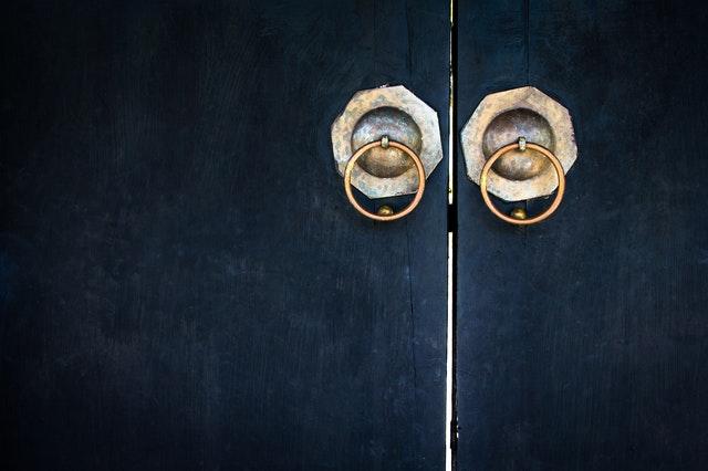 Dverové úchyty zlatej farby na modrých lietacích dverách