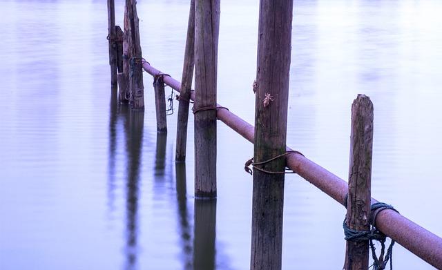 Zábradlie z drevených kolov trčí z vody.jpg