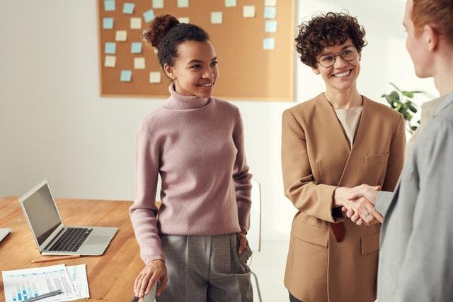 Ženy stoja v kancelárii pri pracovnom stole a podávajú si ruky