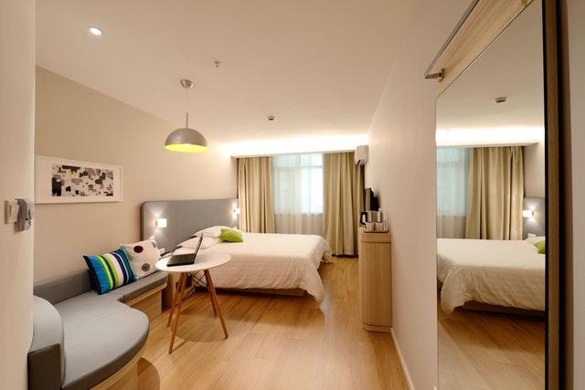 Spálňa s drevenou podlahou a gaučom