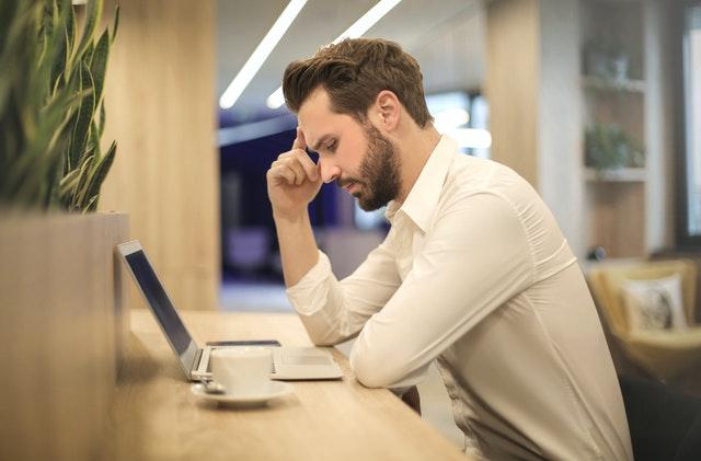 Muž sedí v kancelárii pri stole a tvári sa zamyslene