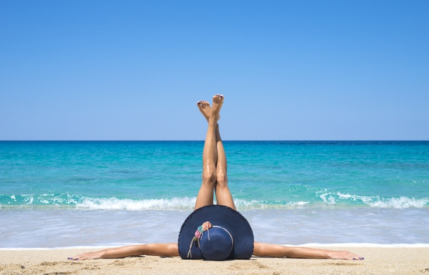 woman-lying-beach-with-legs-up-air_342744-549